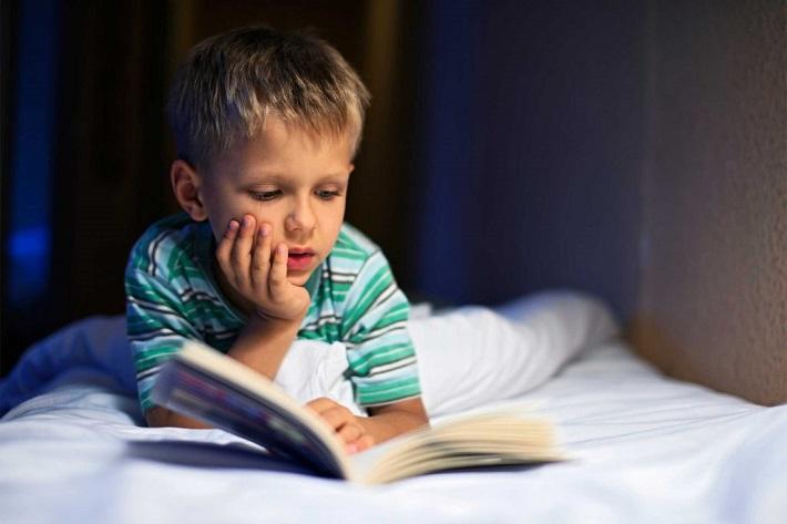 мальчик читает в кровати
